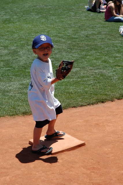 An image of the author playing baseball as a child, wearing a San Diego Padres hat and jersey.