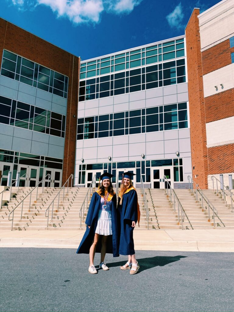 The author and a friend in graduation caps and gowns in front of a brick and glass building