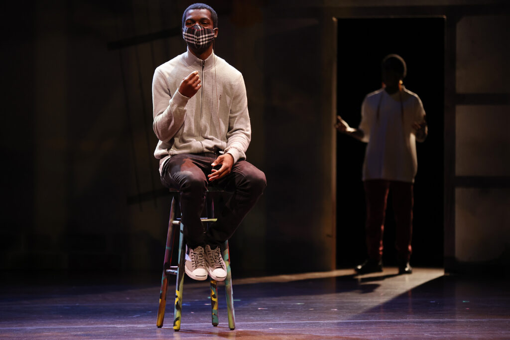 A photograph of Khalil Adams in the performance of Unveiled and Unvarnished.